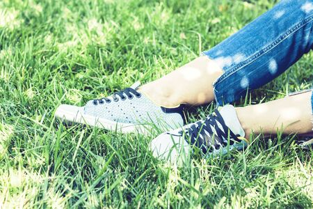 Young woman legs in pair of sport shoes sneakers  of blue suede on the grass lawn in park