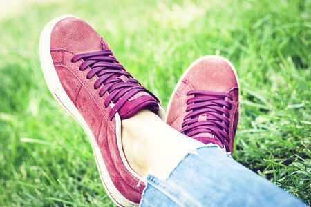 Young woman legs in sport shoes sneakers of pink suede, sitting on the grass lawn in park