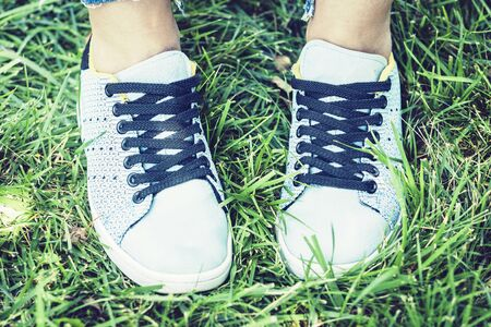 Young woman legs in sport shoes sneakers of blue suede, standing on the grass lawn in park
