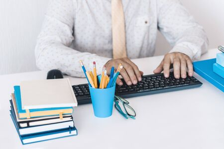 Close-up of hands middle-aged man in white shirt and yellow tie typing on keyboard laptop computer, plastic blue holder with pencils and pens, stack of books, notebooks, smartphone, glasses on white table, education office concept background