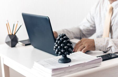 Close-up of hands middle-aged man in white shirt and yellow tie typing on keyboard laptop computer, concrete holder with pencils and pens, notebook, smartphone, glasses and black paperweight on white table, education office concept background Stockfoto