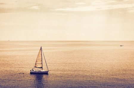 Sunset sea view with sailboat, motor boat from Taormina, Sicily, Italy