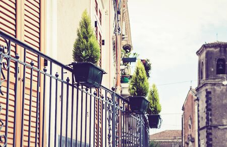 Beautiful cityscape of Italy, decorative plant in pots on historical street of Acitrezza, Catania, Sicily