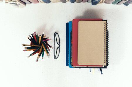 Stapel von Notizbüchern, Stapel von Büchern zurück zum Schulhintergrund, Lehrbücher, Brillen und Bleistifte im Halter mit Kopienraum für Text Standard-Bild