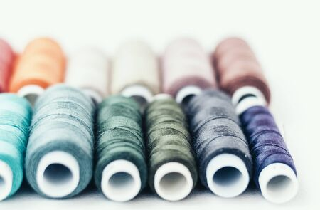 Colored sewing thread coils on white background with copy space for text Zdjęcie Seryjne
