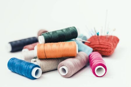 Tools for needlework, red knitted needle pad for sewing and colored thread coils on white background with copy space for text