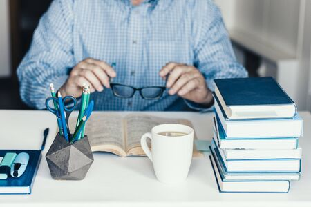 Middle aged man in blue shirt reading book on modern stylish work place with office supplies, glasses, notebooks and books, desk work concept in white and blue colors Zdjęcie Seryjne