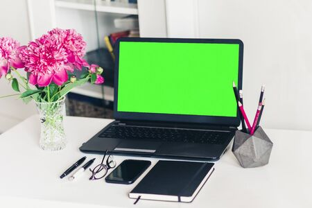 bouquet of pink peonies, green screen laptop, smartphone, pens, glasses and a notebook on a white table, top view