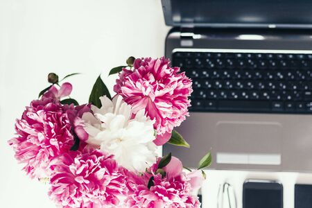 bouquet of pink peonies, laptop, smartphone, pens, glasses and a notebook on a white table, top view