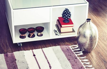 Cozy home interior decor, burning spa aroma candles in coconut shell, metal vase, pile of books, on white glass nightstand near a multi-colored rug
