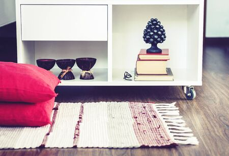 Cozy home interior decor, burning spa aroma candles in coconut shell, metal vase, pile of books, on white glass nightstand near a multi-colored rug with decorative pillows background Zdjęcie Seryjne