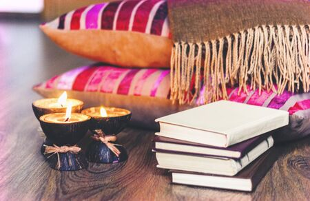 Burning spa aroma candles in coconut shell, plaid and books, cozy home interior background Zdjęcie Seryjne