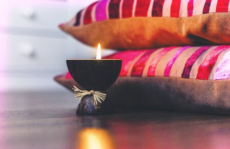 Burning spa aroma candle in coconut shell and  burgundy pillows with pattern, cozy home interior background Zdjęcie Seryjne