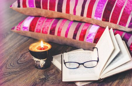 Burning spa aroma candles in coconut shell, pillows, glasses and books, cozy home interior background