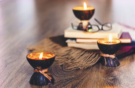 Burning spa aroma candles in coconut shell, plaid, glasses and books, cozy home interior background Zdjęcie Seryjne