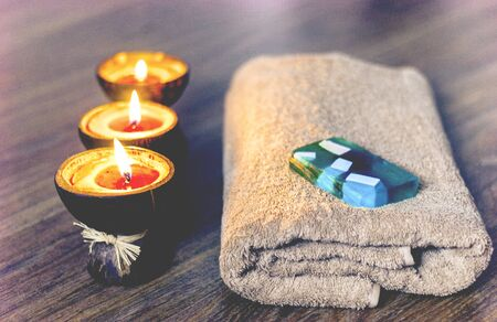 Burning spa aroma candles in coconut shell, handmade soap and towel, spa concept background Zdjęcie Seryjne