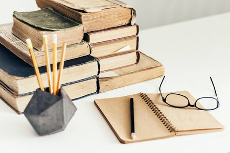 Stack of old books, open notebook, glasses and pencils in holder, education concept background, many books piles with copy space for text Zdjęcie Seryjne