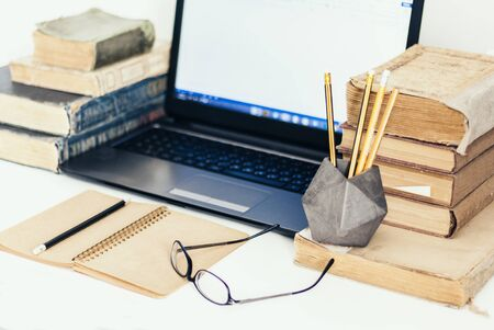 Stack of old books, laptop, glasses and notebook, retro office business background for education learning concept