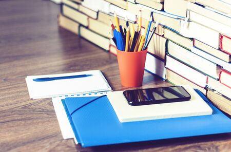 Smartphone, notebook, copybook stack with plastic holder pencils, pens, markers with stack of books education concept background