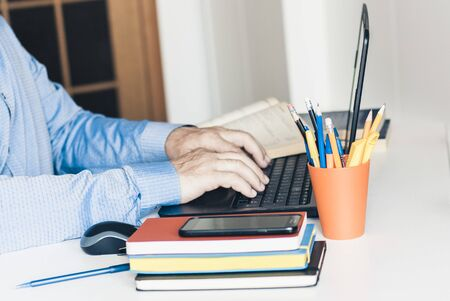 Middle aged man in blue shirt using laptop on modern stylish work place with office supplies, glasses, notebooks and books, desk work concept in white and blue colors