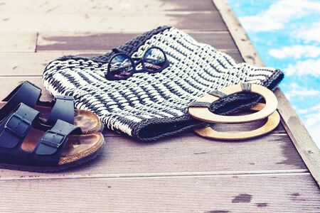 Vintage summer wicker straw beach bag, sun glasses and slippers near swimming pool, tropical background