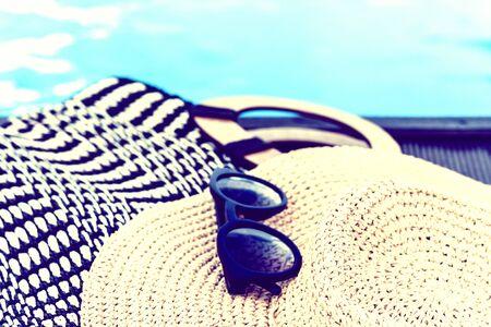 Vintage summer wicker straw beach bag, sun glasses, hat near swimming pool, tropical background Stockfoto