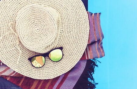 Vintage summer wicker straw beach hat, sun glasses and cover-up beachwear wrap near swimming pool, tropical background Zdjęcie Seryjne