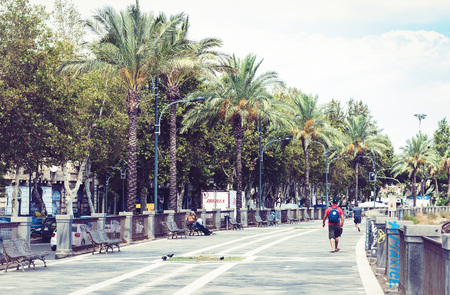 Catania, Sicily, Italy - August 16, 2018: people walking on palm tree alley with metal benches in park Publikacyjne