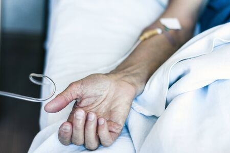 Hand of patient in serious condition is given a medicine through a dropper (healthcare background with an intravenous system)
