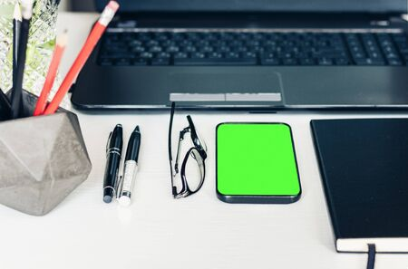 green screen smartphone, laptop, notebook, pencils in holder and glasses in office business background for education learning concept