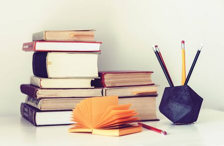 Stack of books and pencils in holder, education concept background, many books piles with copy space for text