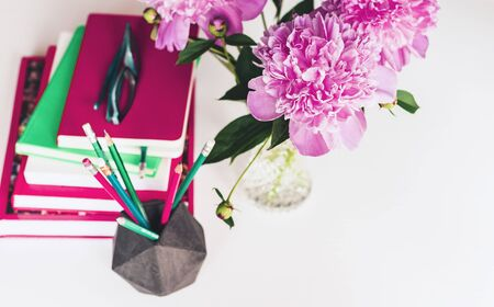 bouquet of pink peonies, a stack of books, pencils and a notebook on a white table, top view