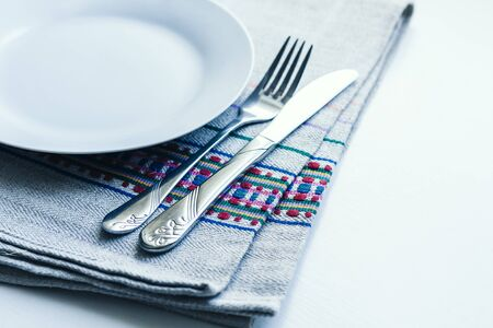 Table setting for dinner: a white plate, a fork, a knife on a woven cloth napkin with an embroidered pattern,  traditional handmade in Ukraine Фото со стока - 133672359