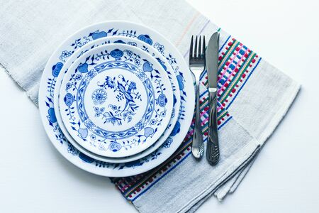 Table setting for dinner: a white plate, a fork, a knife on a woven cloth napkin with an embroidered pattern,  traditional handmade in Ukraine Фото со стока - 133672361