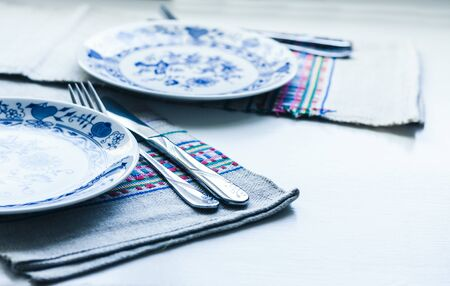 Table setting for dinner: a white plate, a fork, a knife on a woven cloth napkin with an embroidered pattern,  traditional handmade in Ukraine Фото со стока - 133672362