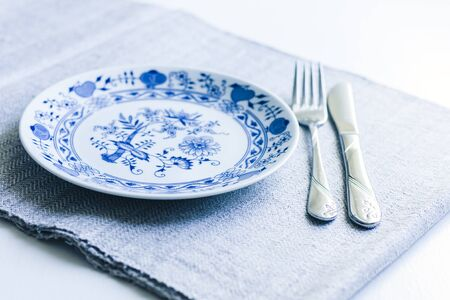 Table setting for dinner: a white plate, a fork, a knife on a woven cloth napkin with an embroidered pattern,  traditional handmade in Ukraine Фото со стока - 133672364