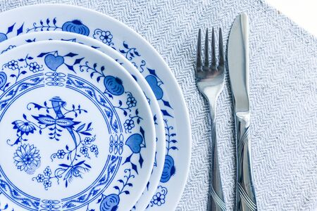 Table setting for dinner: a white plate, a fork, a knife on a woven cloth napkin with an embroidered pattern,  traditional handmade in Ukraine Фото со стока - 133672368