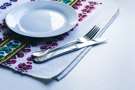 Table setting for dinner: a white plate, a fork, a knife on a woven cloth napkin with an embroidered pattern,  traditional handmade in Ukraine Standard-Bild - 133672374