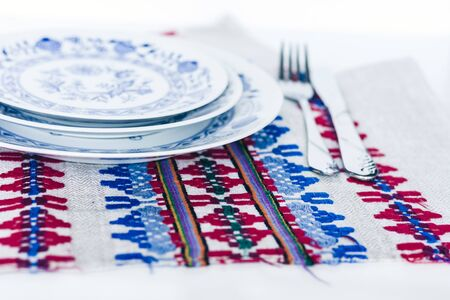 Table setting for dinner: a white plate, a fork, a knife on a woven cloth napkin with an embroidered pattern,  traditional handmade in Ukraine Standard-Bild - 133672380