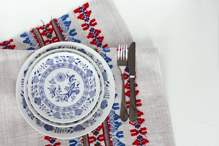 Table setting for dinner: a white plate, a fork, a knife on a woven cloth napkin with an embroidered pattern,  traditional handmade in Ukraine Фото со стока - 133672387