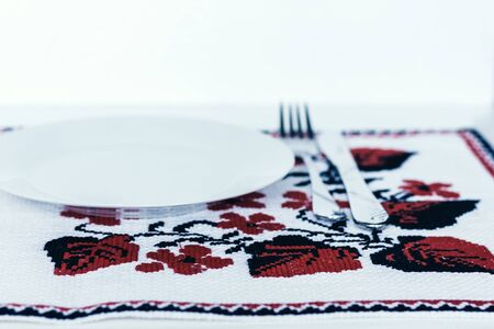 Table setting for dinner: a white plate, a fork, a knife on a woven cloth napkin with an embroidered pattern,  traditional handmade in Ukraine Standard-Bild - 133672404