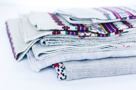 A stack of woven linen towels with embroidery, traditional handmade in Ukraine