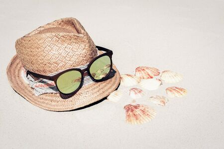 Vintage wicker straw hat and sun glasses on a tropical beach, sea summer concept