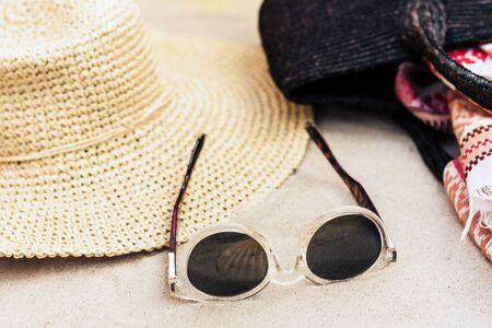Vintage summer wicker straw beach bag, sun glasses, hat, cover-up beachwear wrap on the sand, tropical background Фото со стока - 133672676