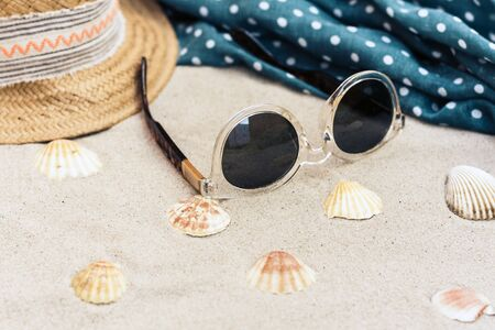Vintage summer wicker straw beach hat, sun glasses, cover-up beachwear wrap on the sand, tropical background Фото со стока - 133672678