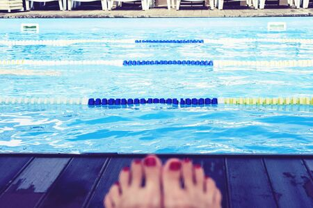female legs on the background of the swimming pool on a summer sunny day Фото со стока - 133673173