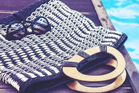 Vintage summer wicker straw beach bag, sun glasses near swimming pool, tropical background