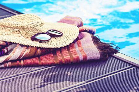 Vintage summer wicker straw beach hat, sun glasses, cover-up beachwear wrap near swimming pool, tropical background Фото со стока - 133673179