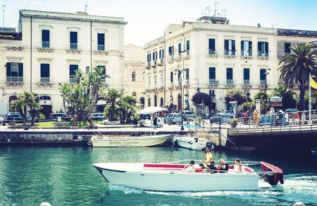 Syracuse, Sicily, Italy – august 12, 2018: square near old port, seafront of Ortygia (Ortigia) Island, tourists in pleasure boat