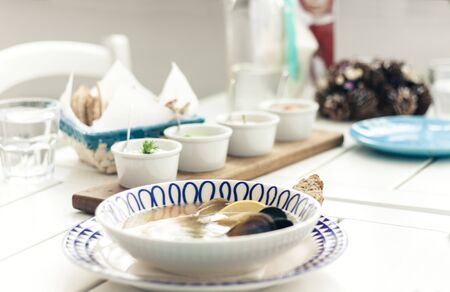 Seafood soup with mussels, prawns and fish in white bowl with blue ornament with sauce in small bowls for traditional meze dinner on the wooden table on background